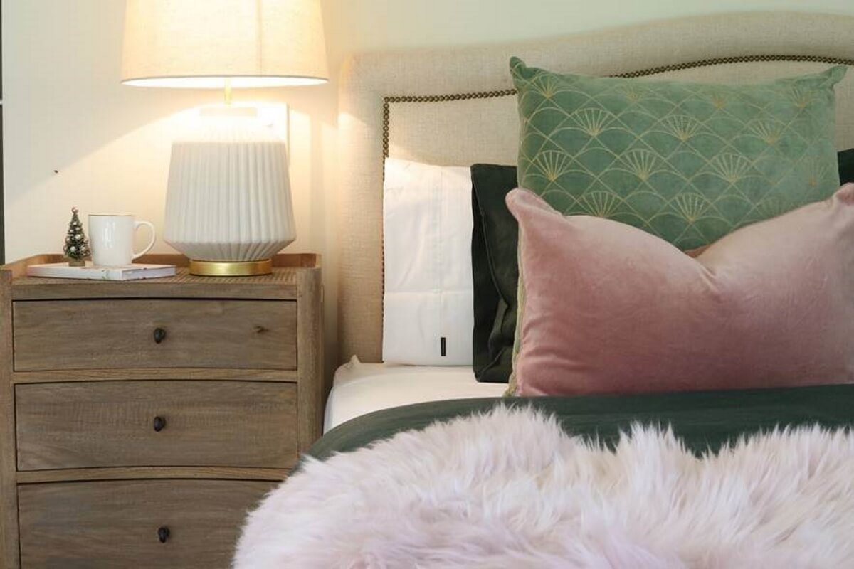 The master bedroom features a soft palette of shell pink and forest green