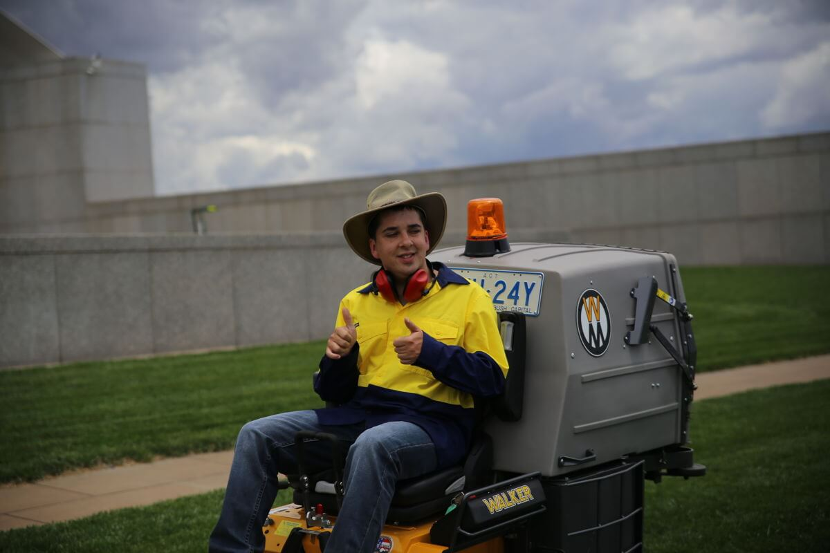 Photo of Joshua Ball mowing parliment house