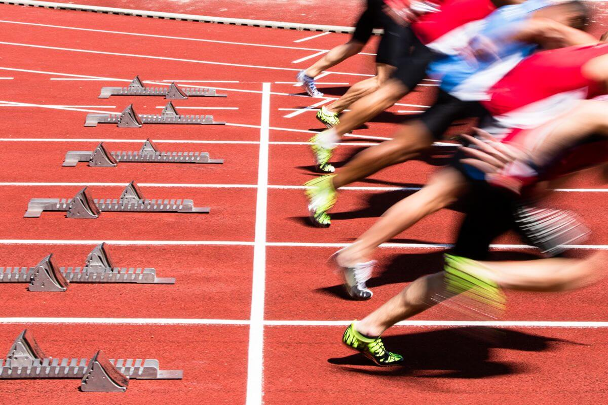 Photo of track sprinters leaping out of starting blocks